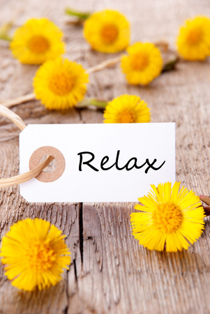 healthfulness: White Tag with the Word Relax on it and many yellow Flowers