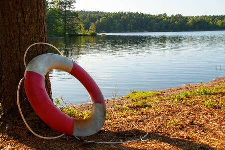 health risk: Lifesaver in the Nature on a Lake with green Trees around, summer Stock Photo