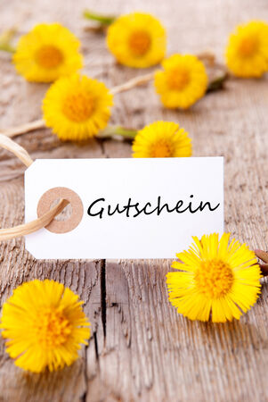 Tag with the German Word Gutschein which means Voucher and many yellow Flowers photo