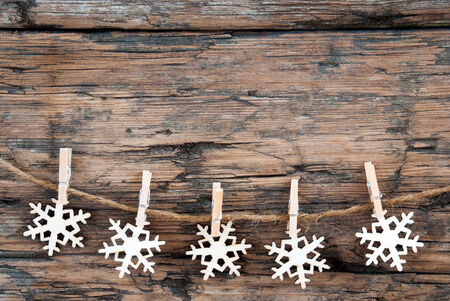 Wooden Snowflakes on a Line on Wood, Christmas Background photo