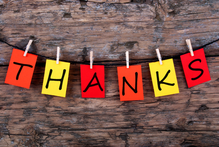 The Word Thanks on Colorful Tags on a Line on Wood photo