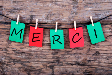 The French Word Merci which means Thanks on a Line on wood photo