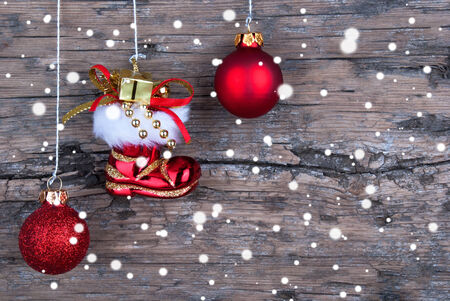 Christmas Balls and a Santa Claus Boots in Front of a Tree Board with Snowflakes photo