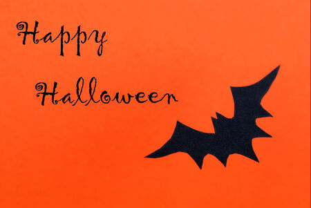Happy Halloween written on an orange Background with a black Bat photo