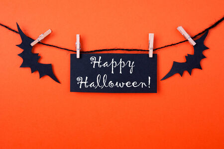 Orange Background with a Black Label and two Bats on a Line with Happy Halloween on it photo