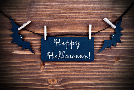 Happy Halloween written on a Tag on a Wooden Background photo