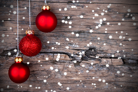 Three Red Christmas Balls on Wood with Snow, Christmas and Winter Background photo