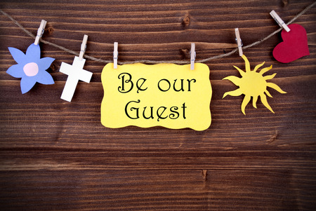 Hanging Tag with the Words Be Our Guest and Some Symbolics on Wood photo