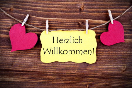 willkommen: Yellow Label with the German Words Herzlich Willkommen which means Welcome, Hanging on a Line with Hearts