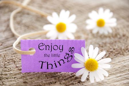 Una etiqueta de color p�rpura con el refr�n disfrutar de las peque�as cosas y las flores en el fondo