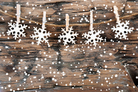 Wooden Snowflakes on a line with Snowflakes on Wood, Christmas or Winter Background photo