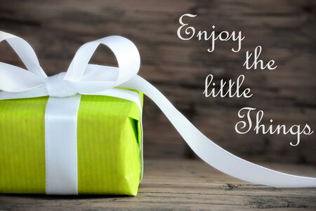 Green Gift with the Saying Enjoy the Little Things on wooden Background photo