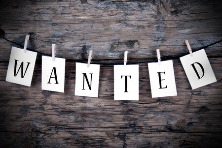 The Word Wanted on White Labels Hanging on a Line on Wooden Background photo