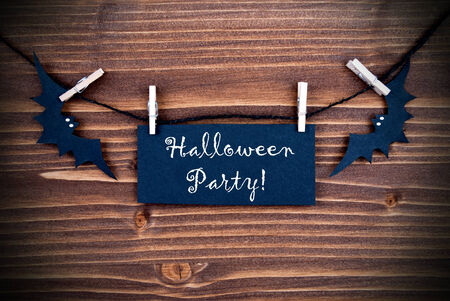 Black Label with the Words Halloween Party Hanging on a Line with Bats on Wooden Background photo