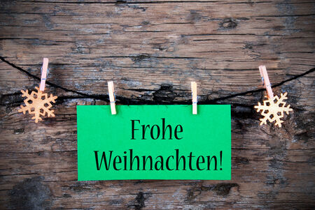 A Green Hanging Tag with the German Words Frohe Weihnachten which means Merry Christmas on wooden Background photo