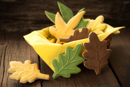 Fall Cookies in different Autumnal Colors in a Cup on Wood photo