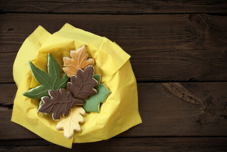 bickie: Different Autumnal Cookie Leaves in a Yellow Bowl on Wood