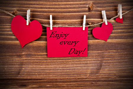 The Saying Enjoy every Day on a red Label with Hearts Hanging on a Line on a Wooden Background photo