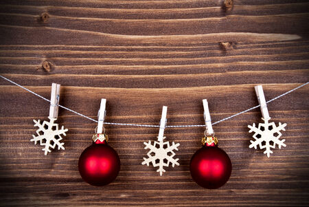Christmas Balls and Snowflakes Hanging on a Line on Wood, Christmas or Winter Background with Copy Space photo