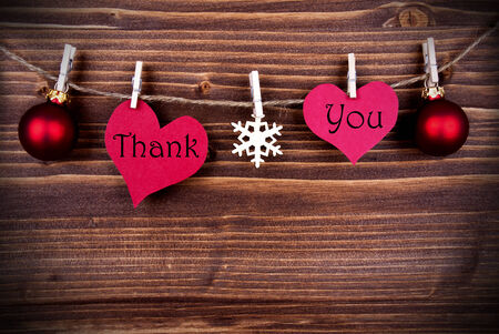 The Words Thank You on two Heart with Christmas or Winter Decoration Hanging on a Line on Wooden Background, with Copy Space photo