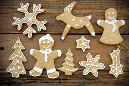 Gingerbread Cookies with White Decoration on Wood, Christmas and Winter Background photo