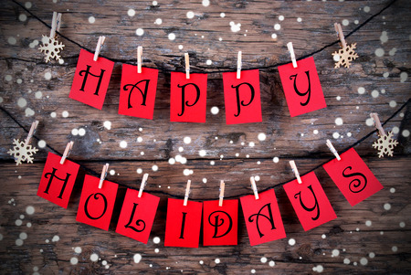 holiday backgrounds: Red Tags with Happy Holidays on it Hanging on a Line on Wood with Snow, Christmas or Winter Holiday Greetings Stock Photo