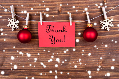 Winter or Christmas Background with the Words Thank You on a Red Label Hanging on a Line in the Snow photo