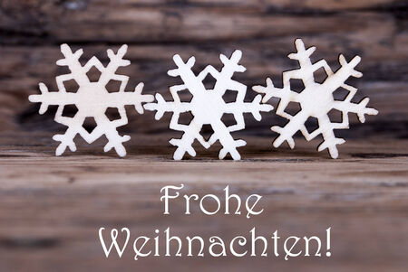 frohe: Three Wooden Snowflakes with the German Words Frohe Weihnachten which means Merry Christmas
