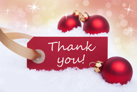 A Red Label in the Snow with the Words Thank You on it as a Winter Background Stock Photo