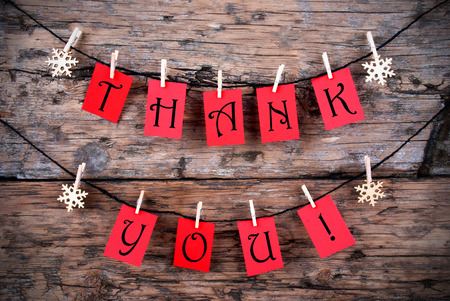 Thank You on Red Tags Hanging on a Line in front of a wooden Background