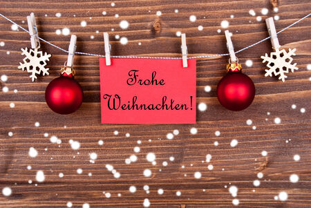 frohe: Red Label in the Snow Hanging on a Line with the German Words Frohe Weihnachten which means Merry Christmas