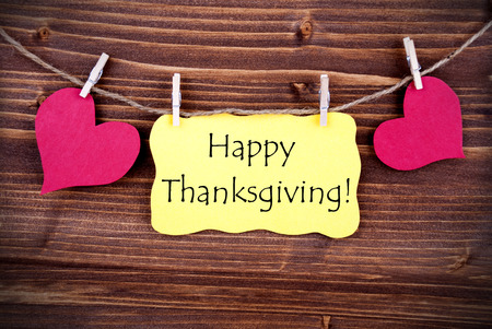 A Yellow Tag with Happy Thanksgiving and two red Hearts Hanging on a Line on Wooden Background photo