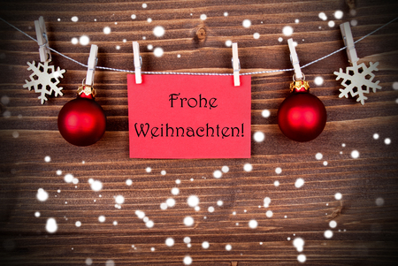 frohe: The German Words Frohe Weihnachten, which means Merry Christmas, on a Red Label hanging on a Line in the Snow Stock Photo