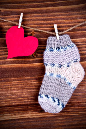 familiar: Baby Stocking Hanging on a Line together with a red Heart, on Wood