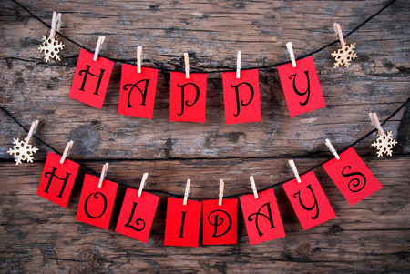 holiday backgrounds: Happy Holidays Greetings on red Tags Hanging on a Line with Snowflakes, Christmas or Winter Background