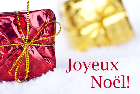 The French Christmas Greetings Joyeux Noël which means Merry Christmas in the Snow with Christmas Gifts