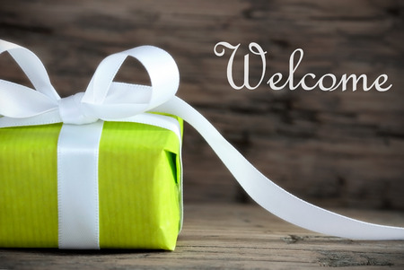 warm welcome: Green Gift with the Word Welcome, on Wooden Background