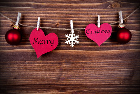 Merry Christmas Greetings on two Hearts Hanging on a Line with Christmas Decoration on Wood with Copy Space photo
