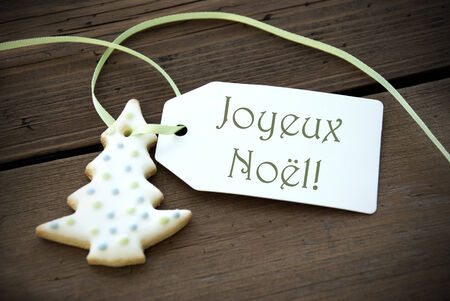 joyeux: A Christmas Tree Cookie with a Label with the French Words Joyeux Noel on it which means Merry Christmas Stock Photo