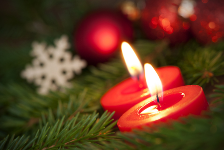 awry: Macro of two red Burning Candles giving a warm Light to the Christmas Decoration in the Background