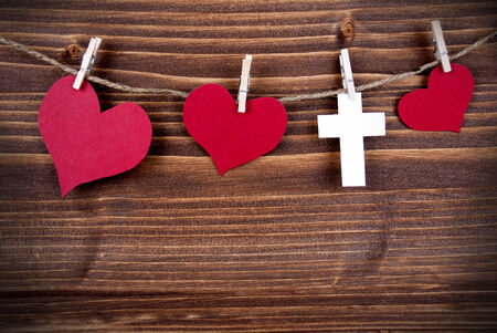 On A Wooden Background Hanging red Hearts and a white Cross on a Line photo