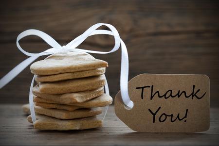 Ginger Bread Cookies mit einer weißen Schleife und einem Etikett, auf dem steht Danke, auf Holzuntergrund