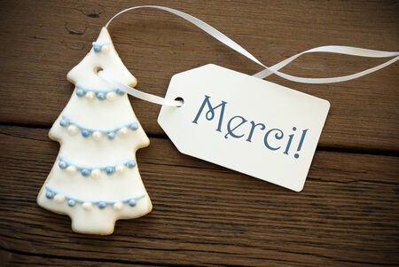 Blue and White Christmas Tree Cookie with white Label with the Blue French Word Merci on it which means Thanks photo