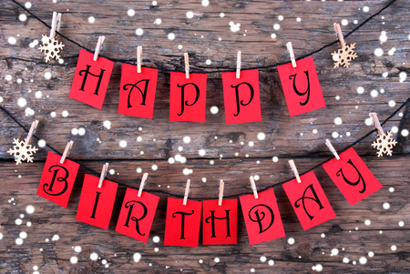Many Red Tags with Happy Birthday Wishes on a Line Hanging in the Snow in front of a Rustic Wooden Panel photo