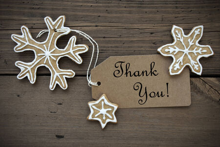 Brown Banner with Thank You on it and Ginger Bread Snowflakes with white Decoration on Wooden Background photo