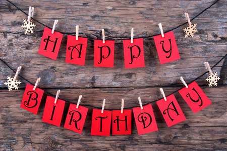 Red Tags Hanging on a Line with the Words Happy Birthday on it, Wooden Background photo