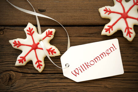 willkommen: Red White Christmas Star Cookies with a Label on which stands the German Word Willkommen which means Welcome