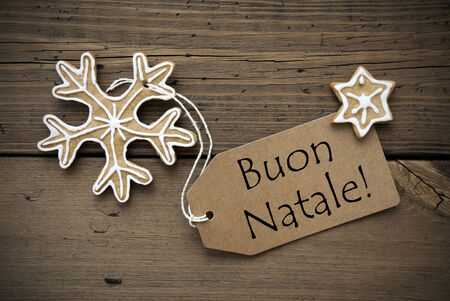 buon: The Italian Words Buon Natale, which means Merry Christmas on a Label with some Ginger Breads on Wood Stock Photo
