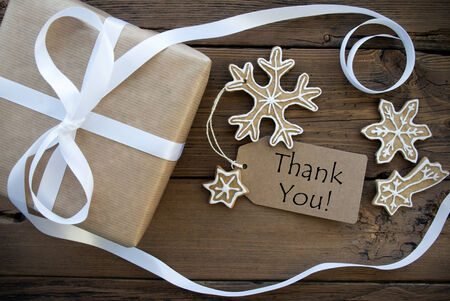 Thank You on a Tag with Christmas Decoration as a brown Gift and decorated Ginger Bread Cookies on Wooden Background photo