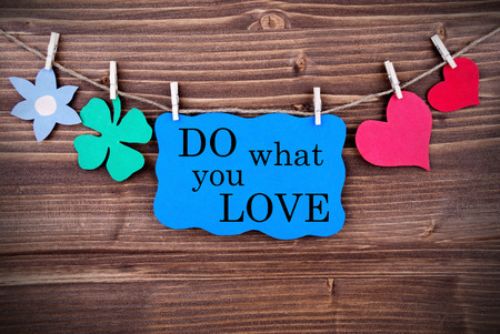 Blue TagWith Phrase Do What You Love On It Hanging on a Line with Different Symbols Like A Flower, Four-leaf Clover And A Heart On Wooden Background photo